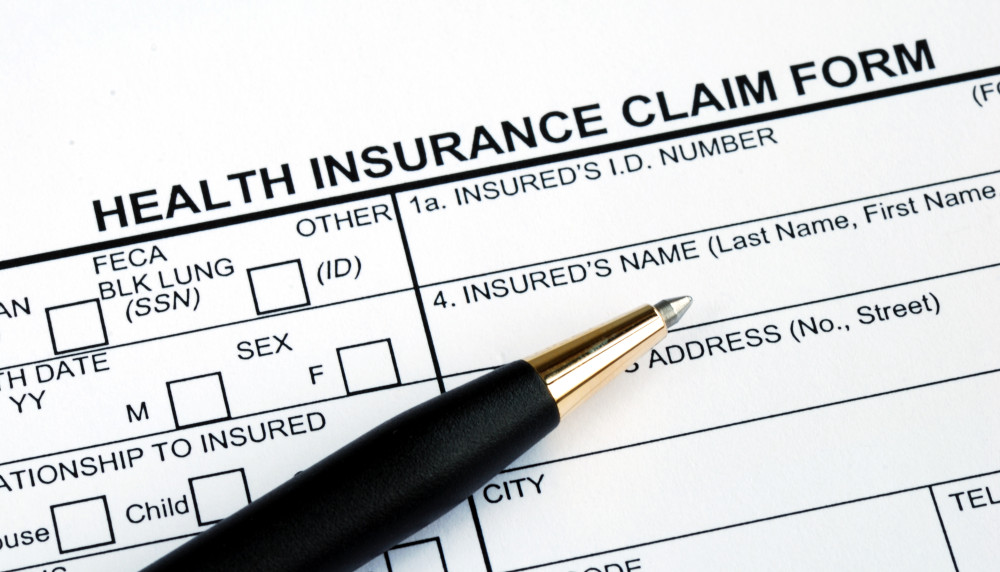 Filling the health insurance claim form with a pen
